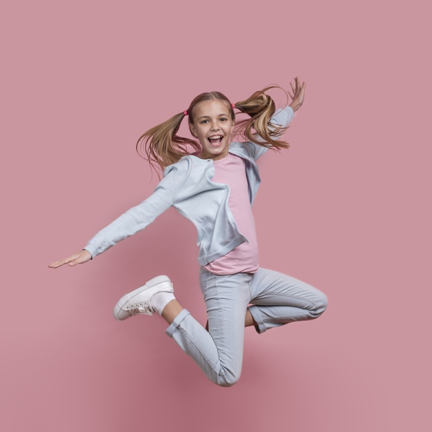 girl-with-pony-tails-jumping-smiles