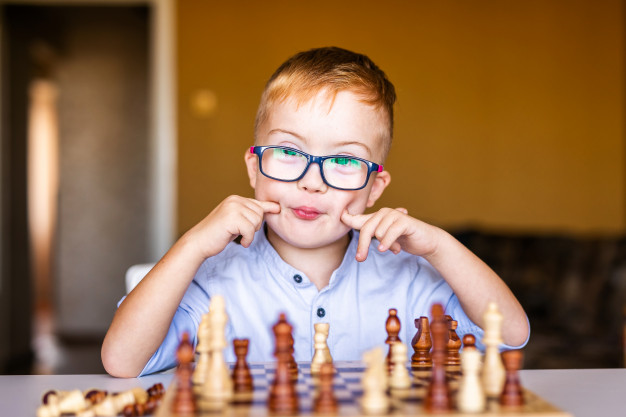 boy-with-down-syndrome-with-big-glasses-playing-chess_88194-771