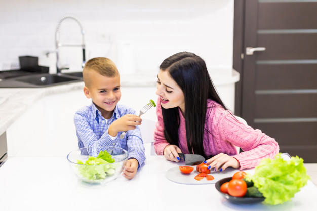 young-mother-with-son-boy-cooking-salad-mom-sliced-vegetables-food-son-give-mother-tasting-salad-happy-family-cook-food-enjoyment-lifestyle-kitche